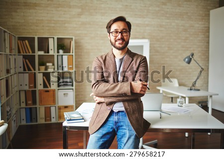 Asian businessman standing by his desk in office