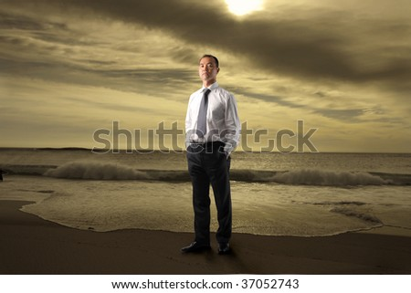 asian businessman standing on the beach - stock photo