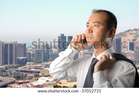 asian businessman talking at the mobile phone against a city view