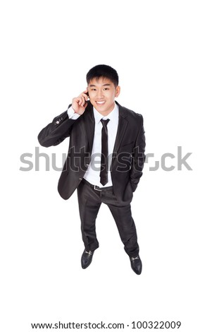 Asian businessman talking mobile cell phone, happy smile looking up, using cellphone, top view full length portrait of young business man phone call, wear elegant suit isolated over white background