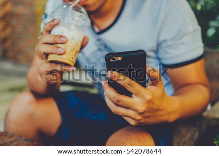 Asian businessman using smartphone and laptop computer at outdoor cafeteria, golden sunset background. VINTAGE TONE