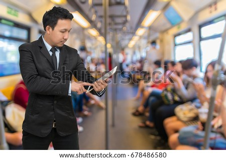 Asian businessman using the tablet over the Abstract blurred photo of passengers who are using the smart phone or tablet in sky train, Business technology and transportation concept