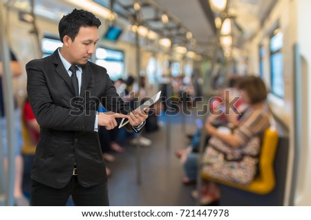Asian businessman using the tablet over the Abstract blurred photo of passengers who are using the smart phone or tablet in sky train, Business technology and transportation concept #721447978