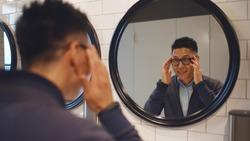 Asian businessman visiting public restroom in restaurant or business center