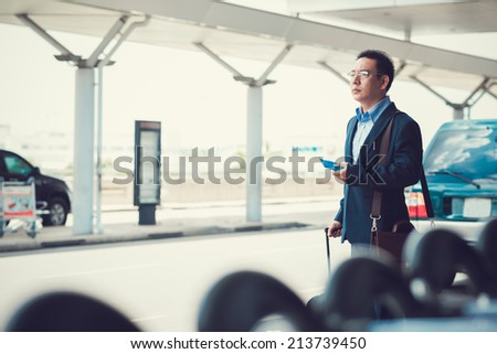 Asian businessman waiting for taxi at the airport