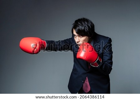 Asian businessman wearing boxing gloves and punching.