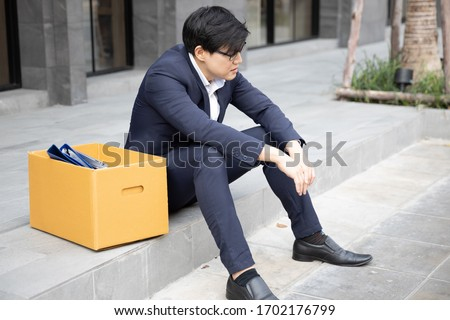 Asian businessman with cardboard box Sitting by the aisle. Unemployment crisis, corona virus covid-19 pandemic impact Asia Thailand. Business shutdown, Unemployed dismissed concept