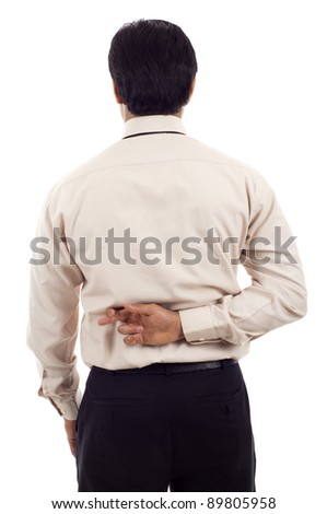 Asian businessman with fingers crossed behind back isolated over white background