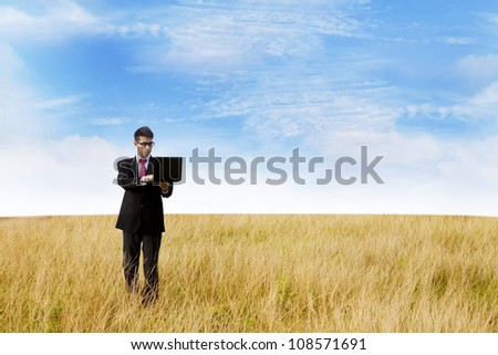 Asian businessman working on laptop computer in the nature