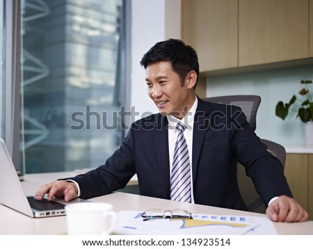 asian businessman working on laptop in office.