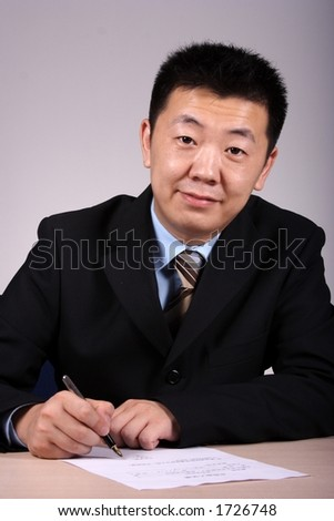 Asian businessman writting a contract. - stock photo
