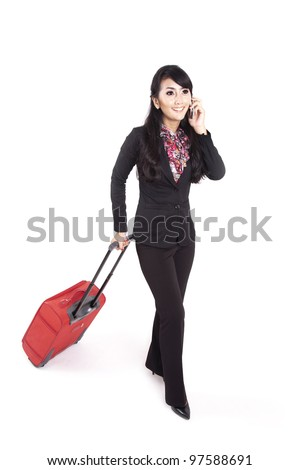 Asian businesswoman carrying suitcase while making a phone call