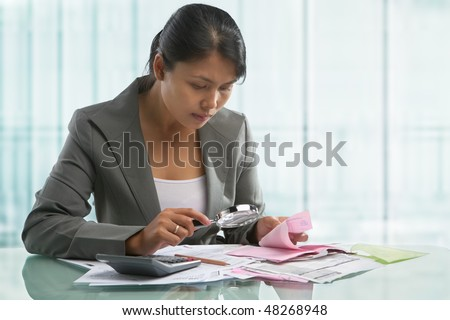 Asian businesswoman checking bills with magnifying glass in the office