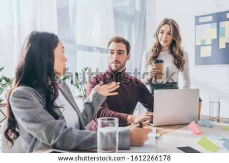asian businesswoman gesturing near coworkers in office