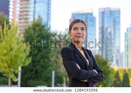 Asian businesswoman. Happy business woman portrait pensive looking up contemplative of her career. City job employment. Chinese professional in black suit confident with crossed arms. #1284193396