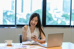 Asian businesswoman in casual suit are glad when completed doing online shopping via smart mobile phone application or technology laptop in modern office, business and lifestyle concept