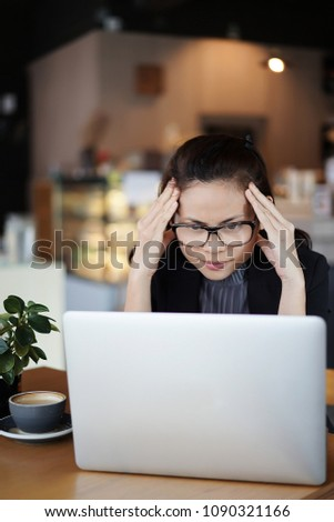Asian businesswoman is looking stressed as she work at her computer, woman holding her head, vertical shot.