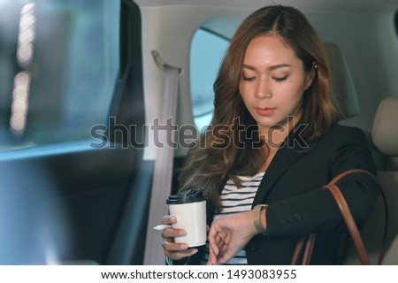 Asian businesswoman looking watch on hand inside the car. Stockfoto ©