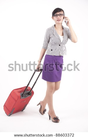 Asian businesswoman pulling a red suitcase while talking on the phone