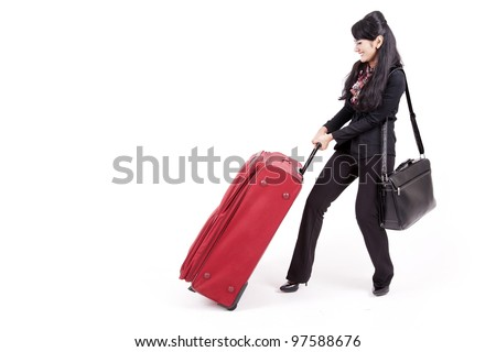 Asian businesswoman pulling heavy suitcase shot in studio isolated on white