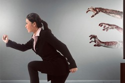 Asian businesswoman running away from zombie's hand coming out of the tv