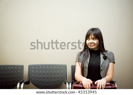 asian businesswoman sitting alone in the waiting room for an appointment