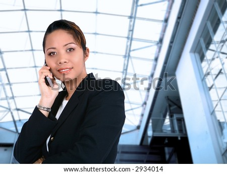 Asian businesswoman talking on the phone, against interior corporate building.