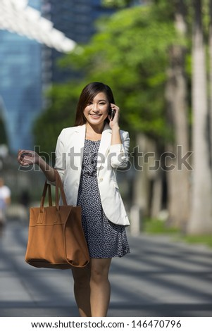 Asian Businesswoman using a smart phone. Happy smiling Chinese business woman walking in street using cellphone.