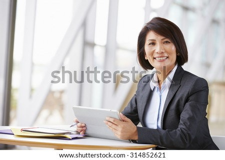 Asian businesswoman with digital tablet,  smiling to camera