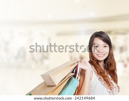 Asian businesswoman with long hair hold shopping bag sale has shopping mall background.Mixed Asian / Caucasian businesswoman.