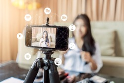 Asian businesswoman working from home live video interaction with customers using camera device vlogging selling make up products, viral internet social media influencer interacting to live audience