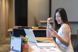 Asian businesswomen hapiness celebrating when checking success goal via technology laptop and mobile phone in modern office or coworking space, technology money wallet and online payment concept