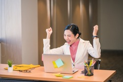 Asian businesswomen hapiness celebrating when checking success goal via technology laptop in modern office or coworking space, Working for pleasure and success