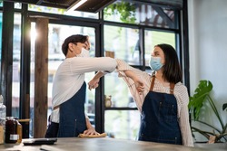 Asian cafe business girl owner wear protective mask, greeting waiter by elbow bump due to Covid 19 pandemic. Attractive beautiful girl feel happy for new normal lifestyles in coffee shop or restaurant