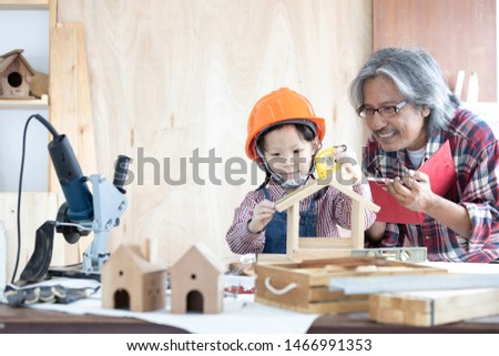 Asian carpenter and daughter working on woodworking table in home carpentry shop, Little asian girl works in home carpentry shop. #1466991353