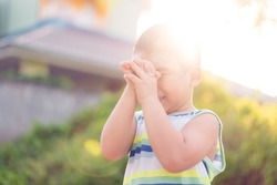 Asian caucasian toddler boy pray in the morning at home.Stay safe and praying to GOD.Online church worship in sunday.Prayer hand with faith, good friday, easter day.praying at home.Hope, peace, faith