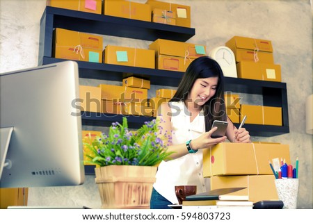 Asian charming beautiful girl entrepreneur looking customer address from her smart phone and writing on packages in modern working room. entrepreneurial self employed business concept.