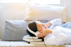 Asian charming beautiful smiling women listens music or relax sound from her headphones and put her head on stack of books in the living room on sofa at the morning time.
