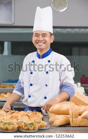 Asian chef or baker posing in front of the pastries in the commercial kitchen
