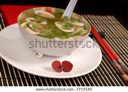 Asian chicken, glass noodle and rice soup with mushrooms and scallions in antique bowl