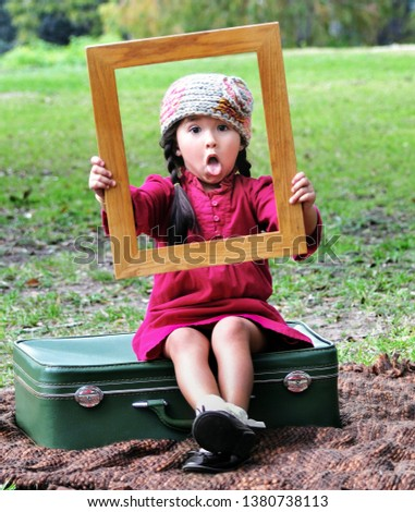 Asian child being silly. Little Asian girl sitting on a vintage suitcase holding a picture frame in front of her face on a fall afternoon, outdoors in New Iberia, Louisiana.