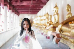 Asian child cute hand in hand or kid girl pay obeisance or respect and pray or raise with gold buddha statue and wear white shirt at temple for peace and buddhist or religious ceremony to happy smile