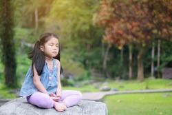 Asian child cute or kid girl close eye mindfulness meditating with breath and sit on stone or rock for peace and yoga relax on nature green garden and red tree at temple park and outdoor warm sunlight