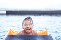 Asian child cute or kid girl smiling swim and wear swimming armband or life jacket with vacation happy fun on pool chair or bed and waterpark for fresh with health exercise and summer holiday travel