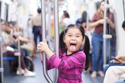 Asian child cute or kid girl stick out tongue enjoy in sky train bogey or electric train with metro railways or subway and holding rail for happy travel or transportation fun in city street on holiday