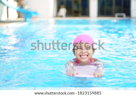 Asian child cute or kid girl wear swimming suit on swimming pool and smile with happy fun in water park for learn and training swim on kick board or refreshing and relax to exercise on summer holiday