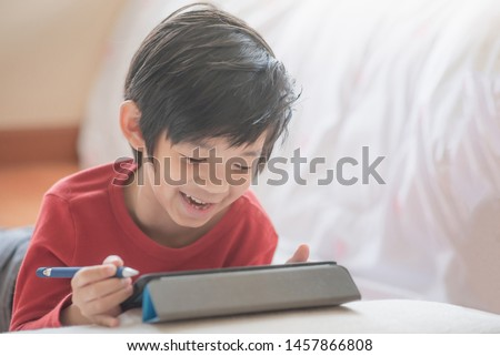 Asian child drawing picture with digital pen on tablet pc computer #1457866808