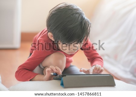 Asian child drawing picture with digital pen on tablet pc computer #1457866811