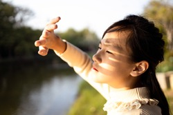 Asian child girl covering face by hand to protect,prevent face skin from bright sun in outdoor summer,female people hand covered the strong sun light feeling hot uncomfortable,risk of eyes damage