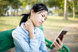 Asian child girl holding smartphone in hand, massage her neck,bending head reated to the pressure on the spine,stiff neck,muscles have pain because play long time or incorrect posture in use phone